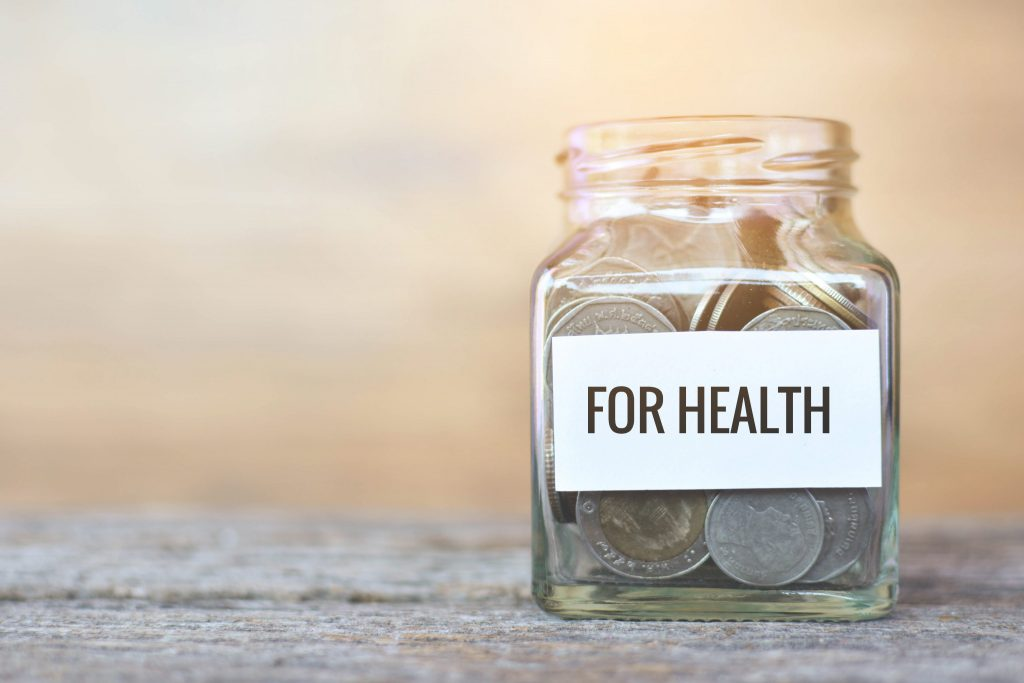 """Money in a glass jar with """"health"""" word."""