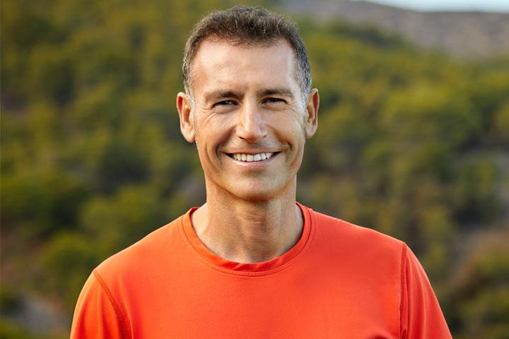 man smiling in orange shirt